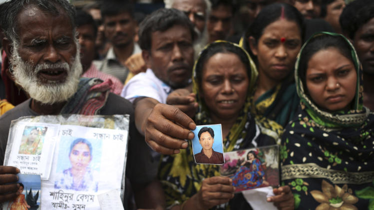 A man holds out a picture of his missing relative on Monday April 29, 2013 in Savar, near Dhaka, Bangladesh. Rescue workers in Bangladesh gave up hopes of finding any more survivors in the remains of a building that collapsed five days ago, and began using heavy machinery on Monday to dislodge the rubble and look for bodies - mostly of workers in garment factories there. At least 381 people were killed when the illegally constructed, 8-story Rana Plaza collapsed in a heap on Wednesday morning along with thousands of workers in the five garment factories in the building.(AP Photo/Wong Maye-E)