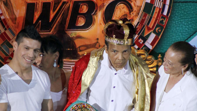 "FILE - In this Monday, Dec. 3, 2012, file photo, the former heavyweight boxing champion Muhammad Ali, center, is crowned ""King of Boxing"" while accompanied by his wife, Lonnie, right, and Argentine boxer Sergio Martinez during the 50th convention of the World Boxing Council in Cancun, Mexico. Spokesman Bob Gunnell said Saturday, Dec. 20, 2014, that the 72-year-old boxing great has been hospitalized with a mild case of pneumonia and is in stable condition. (AP Photo/Israel Leal, File)"