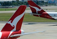 Two Qantas aircraft cross paths at Sydney International Airport, in 2011. Australian flag carrier has announced it will split its international and domestic arms into separate businesses as part of a plan to transform the airline, effective from July