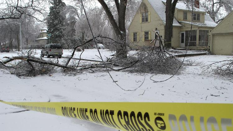Downed power lines are cordoned off with police tape near Phillips Avenue on Wednesday, April 10, 2013, in Sioux Falls, S.D. A spring storm that began Tuesday and was expected to last through Thursday wreaked havoc on roads, downed branches and knocked out power for thousands of residents. (AP Photo/Amber Hunt)
