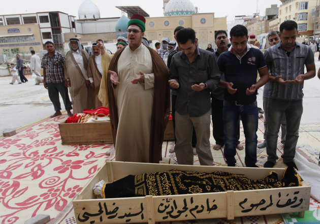 Mourners pray over the two bodies killed in a car bomb attack before their burial in the holy Shiite city of Najaf, 160 kilometers (100 miles) south of Baghdad, Iraq, Monday, May 20, 2013. A wave of c