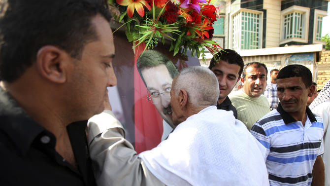 A relative of former Basra governor, Mohammed al-Wailie, kisses his poster during his funeral in Basra, 340 miles (547 kilometers) southeast of Baghdad, Iraq, Friday, Sept. 28, 2012. Gunmen shot dead the former governor, Mohammed al-Wailie, as he was driving his car in the city center, the police said. (AP Photo/Nabil al-Jurani)