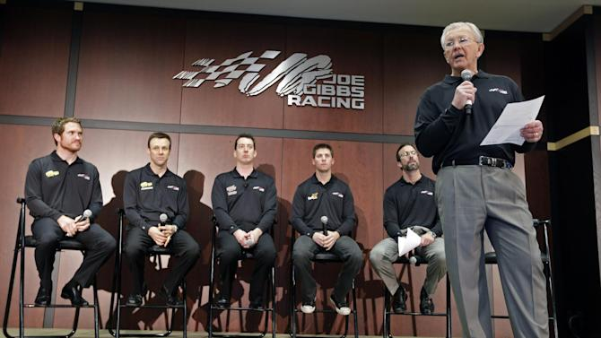 Team owner Joe Gibbs, right, talks to the media as drivers, from left, Brian Vickers, Matt Kenseth, Kyle Busch, and Denny Hamlin, and team president JD Gibbs look on during a news conference at Joe Gibbs Racing in Huntersville, N.C., Thursday, Jan. 24, 2013, as part of the NASCAR Sprint Cup Media Tour. (AP Photo/Chuck Burton)