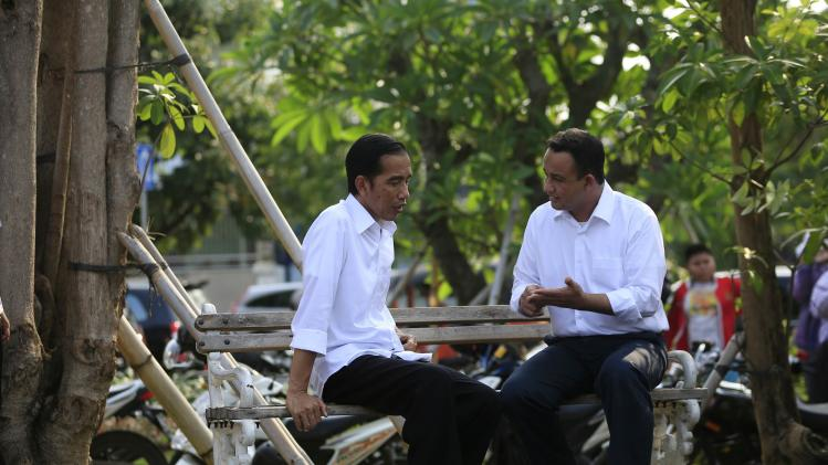 "Indonesian presidential candidate Joko ""Jokowi"" Widodo talks with his colleague while waiting for the results announcement by the Elections Commission, at Waduk Pluit in Jakarta"