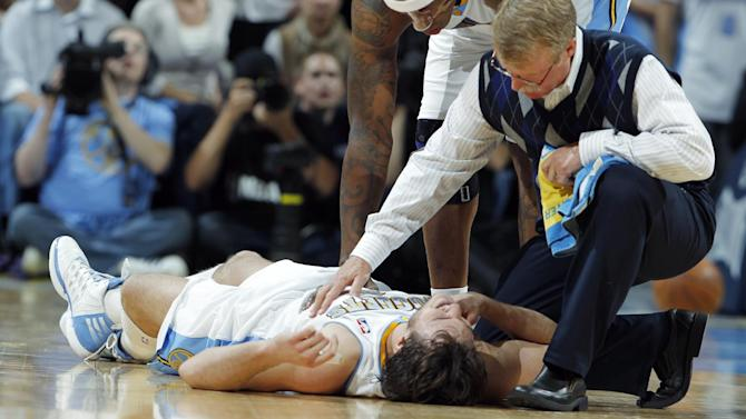 Denver Nuggets forward Danilo Gallinari, left, of Italy, is tended to by head trainer Jim Gillen, front right, and forward Al Harrington after Gallinari was injured when he ran into Los Angeles Lakers forward Pau Gasol in the fourth quarter of the Lakers' 92-88 victory in Game 4 of the teams' first-round NBA  basketball series in Denver on Sunday, May 6, 2012. Gallinari walked off the court and returned to the game. (AP Photo/David Zalubowski)