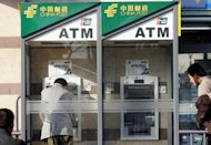 Chinese bank customers use China Postal Savings Bank's ATM machines in Beijing. The head of the bank, one of China's biggest, is under investigation for corruption, a media report said, the second graft case involving bankers to emerge in a month
