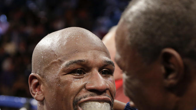 Floyd Mayweather Jr., left, reacts toward his father Floyd Mayweather Sr. after defeating Robert Guerrero by unanimous decision during a WBC welterweight title fight, Saturday, May 4, 2013, in Las Vegas. (AP Photo/Rick Bowmer)