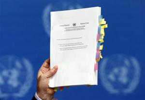 Kirby, Chairperson of the Commission of Inquiry on Human Rights in North Korea, holds a copy of his report during a news conference at the United Nations in Geneva