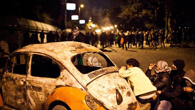 "In this Monday, Jan. 28, 2013 photo, an Egyptian protester take cover beside a vehicle damaged during clashes between protesters and Egyptian security forces in Downtown Cairo, Egypt. On Tuesday, Jan. 29, 2013, Egypt's army chief warns of ""the collapse of the state"" if political crisis continues. (AP/Virginie Nguyen Hoang)"