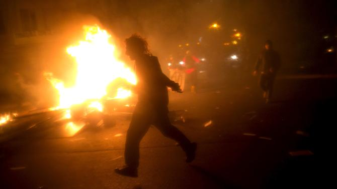 A man runs in front of a burning barricade during a rally against police violence