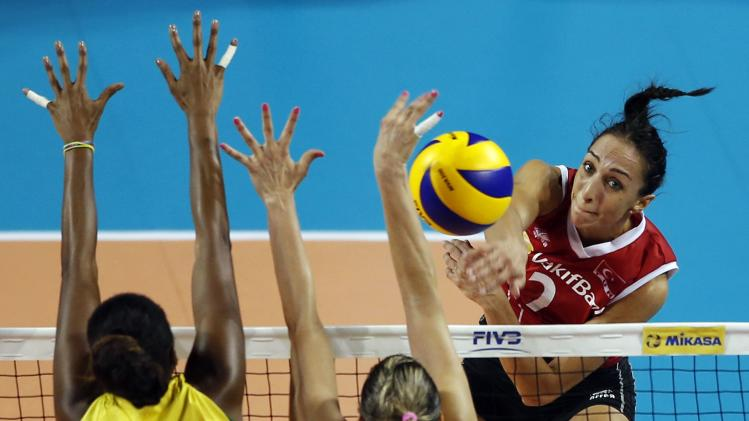 Gozde Sonsirma of Turkey spikes the ball against Danielle Lins and Fabiana Claudino of Brazil during their FIVB Women's Volleyball World Grand Prix 2014 final round match in Tokyo