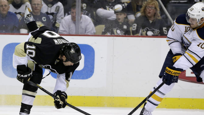 Pittsburgh Penguins left wing Brenden Morrow (10) and Buffalo Sabres defenseman Christian Ehrhoff (10) battle for control of the puck in the second period of an NHL hockey game in Pittsburgh Tuesday, April 2, 2013. (AP Photo/Gene J. Puskar)