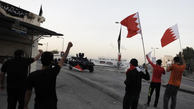 Protesters demonstrating for Salman hold Bahraini flags as a riot police armoured personnel carrier arrives, in the village of Bilad Al Qadeem