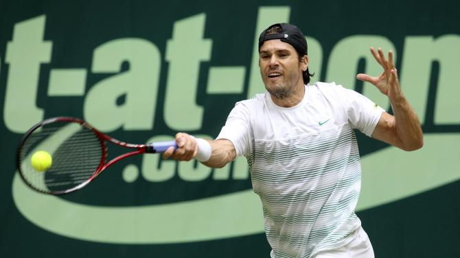 Germany's  Tommy Haas  returns a ball  during his  match against Swiss Roger Federer at the Gerry Weber Open ATP tennis tournament final  in Halle, western Germany, Sunday June 17, 2012.  Wild card Tommy Haas of Germany defeated five-time winner Roger Federer 7-6 (5), 6-4 to win the Gerry Weber Open for the second time on Sunday. The 87th-ranked Haas, the oldest player in the singles draw at 34, recovered from losing his serve in the first game by winning the first set on a tiebreaker and then getting the decisive break in the ninth game of the second set.  (AP Photo/dapd/Joerg Sarbach)