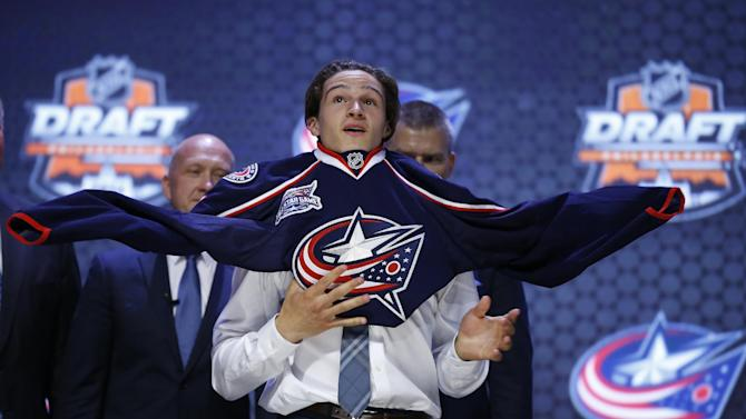 Sonny Milano pulls on a Columbus Blue Jackets sweater after being chosen 16th overall during the first round of the NHL hockey draft, Friday, June 27, 2014, in Philadelphia