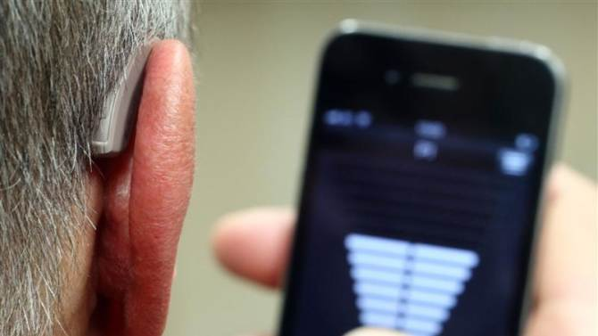 Employee of GN, the world's fourth largest maker of hearing aids, demonstrates the use of ReSound LiNX in Vienna