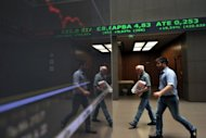 Employees pass an electronic display at the Athens stock exchange. Despite making progress, the eurozone debt crisis remains unsolved and, in a repeat of last summer, could still bring nasty surprises to global stock markets in July and August, analysts said