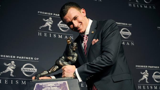 FILE - In this Dec. 8, 2012, file photo, Texas A&M quarterback Johnny Manziel poses with the Heisman Trophy in New York, after becoming the first freshman to win the award. With the NCAA reportedly investigating Manziel for possibly rules violations, could the Heisman Trophy winner be in danger of having the award stripped the way Reggie Bush's was after his NCAA troubles? (AP Photo/Henny Ray Abrams, File)
