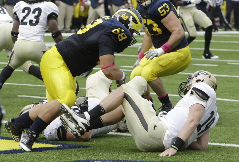 Michigan defensive tackle Mike Martin (68) sacks Purdue quarterback Caleb TerBush (19) in the end zone for a safety during the second quarter of an NCAA college football game in Ann Arbor, Mich., Saturday, Oct. 29, 2011. (AP Photo/Carlos Osorio)