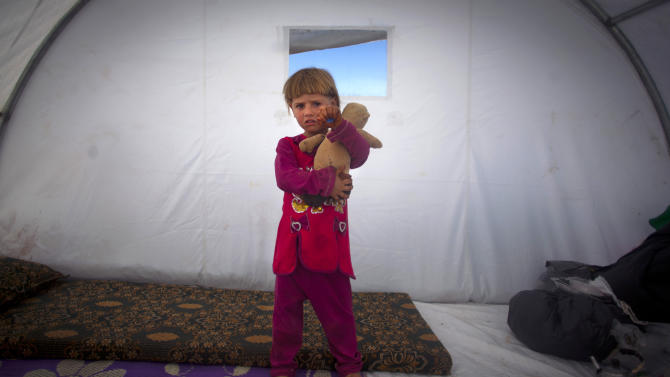 In this Wednesday, Nov. 7, 2012 photo, Amina Al Sado, 5, who fled with her family from the violence in their village, poses for for a photograph inside a tent at a displaced camp, in the Syrian village of Atmeh, near the Turkish border with Syria. Most of the displaced people in the tent camp rising near this village on the Syrian-Turkish border are children. All have fled the violence of Syria's civil war further south. Many have seen violence themselves, some have lost relatives, and most have trouble sleeping and panic when they hear loud noises or airplanes, their parents say. The Atmeh camp was born of necessity about three months ago, say the local rebels who run the place, distributing tents and food aid provided by a smattering of aid organizations.(AP Photo/Khalil Hamra)