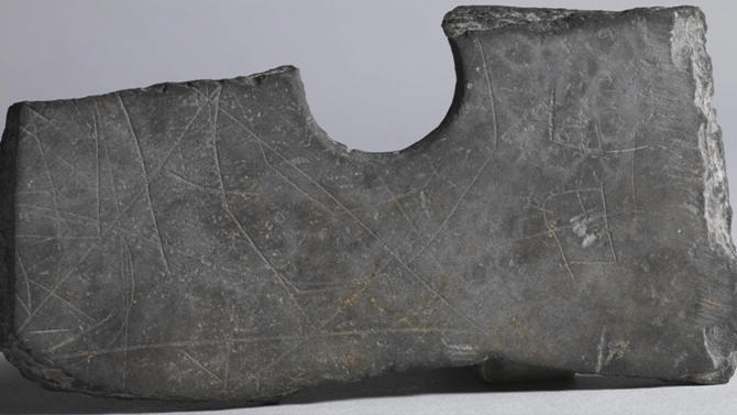 In this undated photo, markings etched on an unearthed piece of a stone ax are seen near Zhuangqiao grave relic, in Pinghu, in eastern China's Zhejiang province. Archaeologists say they have discovered a new form of primitive writing in markings on stoneware excavated from the relic site in eastern China dating 5,000 years back, about 1,400 years earlier than the oldest known written Chinese language. (AP Photo) CHINA OUT