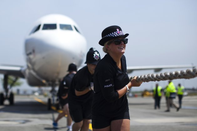 Members of London's Metropolitan Police Ladies tug an Airbus A320 jet for 100 feet during a race at John F. Kennedy International Airport in New York