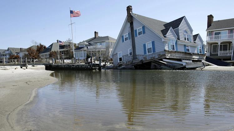 A home rests in Barnegat Bay, Thursday, April 25, 2013, in Mantoloking, N.J., after it was swept away last October by Superstorm Sandy. Six months after Sandy devastated the Jersey shore and New York City and pounded coastal areas of New England, the region is dealing with a slow and frustrating, yet often hopeful, recovery. (AP Photo/Mel Evans)
