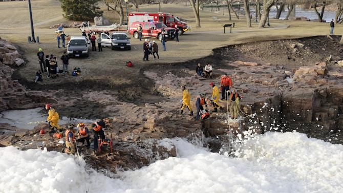 Rescuers search the Big Sioux River for 16-year-old Madison Leigh Wallace and 28-year-old Lyle Francis Eagletail, who were dragged away by the fast-moving, icy river in Sioux Falls, S.D., as they tried to save the girl's 6-year-old brother, Garrett, Thursday, March 14, 2013. The boy was pulled ashore with minor injuries, but his sister and Eagletail are presumed drowned. (AP Photo/The Argus Leader, Elisha Page)  NO SALES