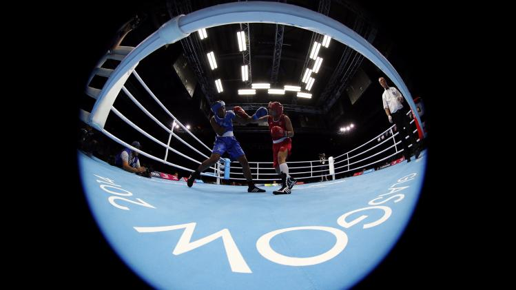 India's Devi exchanges punches with Mozambique's Machongua during their women's Light Weight semi-final boxing match at the 2014 Commonwealth Games in Glasgow