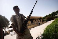 A member of the Libyan security forces secures the area during a visit by the head of Libya's national assembly, Mohammed al-Megaryef, to the US consulate compound in Benghazi. US military and intelligence agencies have launched an elaborate manhunt in Libya against the militants suspected of staging the most serious assault on an American diplomatic mission in decades, officials and experts said