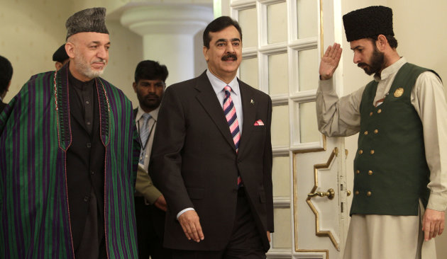 Afghan President Hamid Karzai, left, arrives with Pakistan's Prime Minister Yousaf Raza Gilani, center, at Prime Minister House in Islamabad, Pakistan for bilateral talks on Thursday, Feb. 16, 2012. Karzai arrived in Pakistan for talks on how Islamabad can facilitate peace negotiations with the Afghan Taliban.
