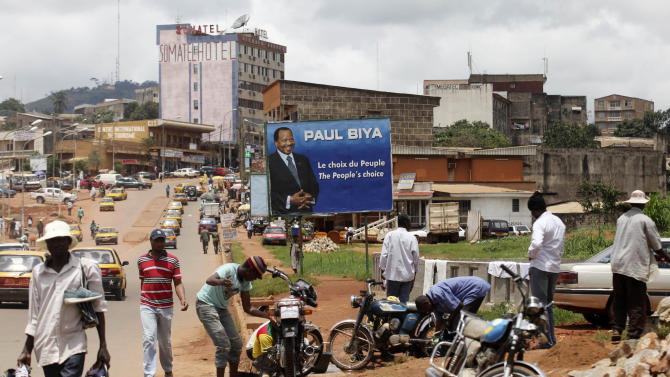 FILE -  In this Oct. 7, 2011 file photo, people walk past a campaign billboard for President Paul Biya, in Yaounde, Cameroon. The party of Cameroon's entrenched ruler won 56 of the 70 contested seats in the nation's first-ever senatorial election, the Supreme Court announced Monday, April 29, 2013. According to the constitution, the 80-year-old Biya, in power since 1982, gets to appoint the remaining 30 members of the legislative body, ensuring total control of the newly-created 100-seat Senate.(AP Photo/Sunday Alamba, File)
