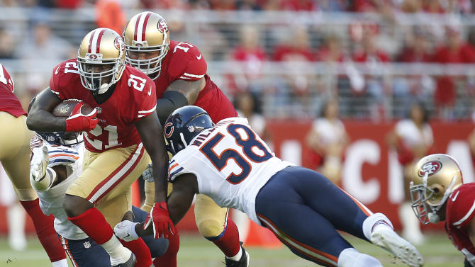 San Francisco 49ers running back Frank Gore (21) runs as Chicago Bears outside linebacker D.J. Williams (58) dives for him during the first quarter of an NFL football game in Santa Clara, Calif., Sunday, Sept. 14, 2014. (AP Photo/Tony Avelar)