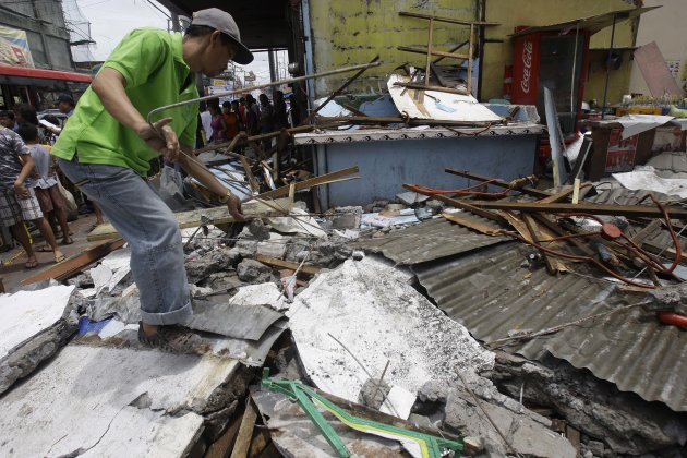 A man salvages steel rods on the rubble of a collapsed wall as it was knocked down by strong winds, killing one man and injuring two others in suburban Novaliches, Quezon City, Philippines, Sunday, Au
