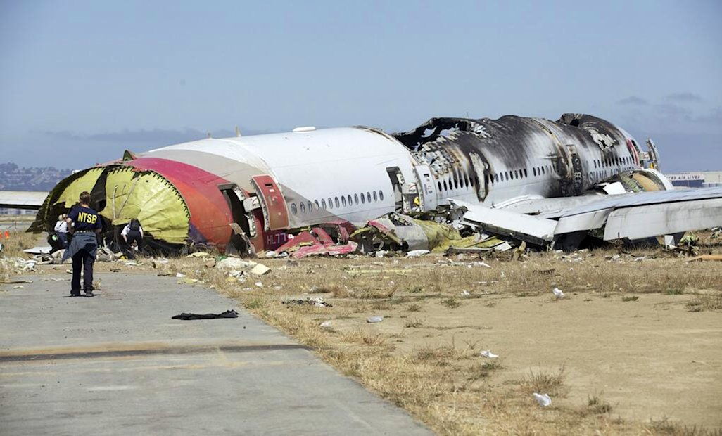 This image released by the National Transportation Safety Board Sunday, July 7, 2013, shows NTSB workers near the Boeing 777 Asiana Airlines Flight 214 aircraft. The Asiana flight crashed upon landing Saturday, July 6, at San Francisco International Airport, and two of the 307 passengers aboard were killed. (AP Photo/NTSB)
