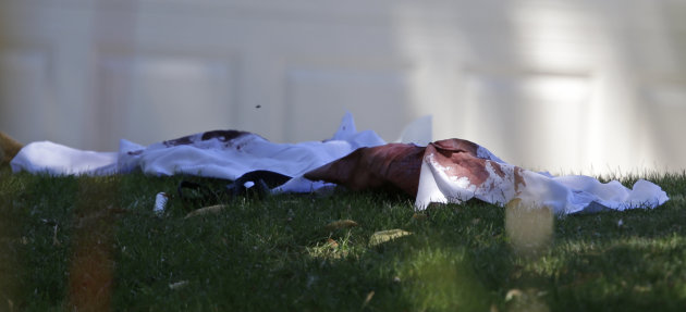 A blood stained piece of clothing is seen on a lawn outside the Sikh Temple in Oak Creek, Wis. where a shooting took place Sunday, Aug 5, 2012. (AP Photo/Jeffrey Phelps)