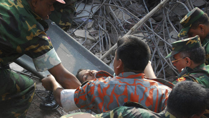 Rescuers carry a survivor pulled out from the rubble of a building that collapsed in Saver, near Dhaka, Bangladesh, Friday, May 10, 2013. Rescue workers in Bangladesh freed the woman buried for 17 days inside the wreckage of a garment factory building that collapsed, killing more than 1,000 people. Soldiers at the site said her name was Reshma and described her as being in remarkably good shape despite her ordeal. (AP Photo/Parvez Ahmad Rony)
