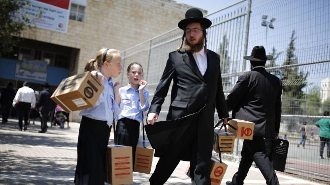 File photo shows an ultra-Orthodox Jewish man walking out with his children after collecting gas mask kits in Jerusalem