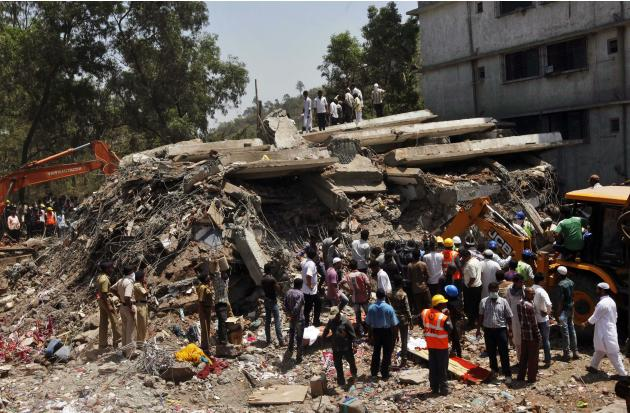 People gather around a heap of debris at the site of a building collapsed as a rescue operation continues on the outskirts of Mumbai, India, Friday, April 5, 2013. A half-finished building that was be
