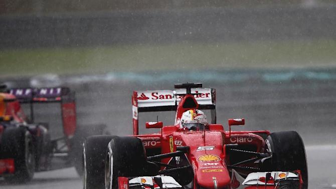 Ferrari driver Sebastian Vettel of Germany steers his car in the rain during the qualifying session for the Malaysian Formula One Grand Prix at Sepang International Circuit in Sepang, Malaysia Saturday, March 28, 2015. Vettel finished second behind Mercedes driver Lewis Hamilton of Britain for Sunday's race. (AP Photo/Thomas Lam)