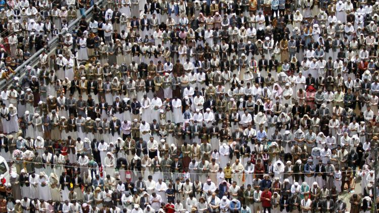 Pro-government protesters perform the weekly Friday prayers during a rally in Sanaa