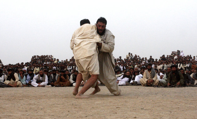 Pakistani and Afghan spectators watch traditional wrestling tournament between Afghans and Pakistani wrestlers at Pakistan-Afghanistan border town of Chaman on Friday, Aug. 24, 2012. (AP Photo / Matiu