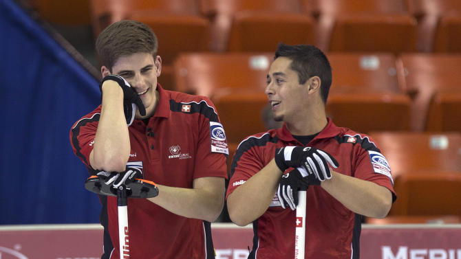 Switzerland's Reto Keller, left, and skip Marc Pfister chat as Switzerland plays Sweden at the men's world curling championships in Halifax, Nova Scotia, on Tuesday, March. 31, 2015. (AP Photo/The Canadian Press, Andrew Vaughan)