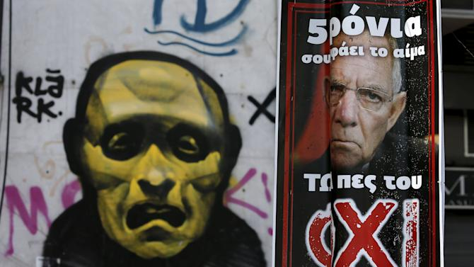 A referendum campaign poster depicting German Finance Minister Schaeuble is seen before a political graffiti in Athens