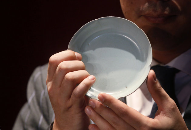 Nicolas Chow, Sotheby's Asia Deputy Chairman, holds the Chinese Song Dynasty ceramics Ruyao Washer at the Sotheby's auction in Hong Kong Wednesday, April 4, 2012. The 900-year-old dish smashed the