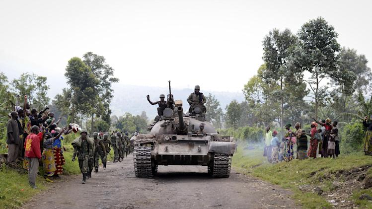 Congolese army soldiers are cheered by residents as they march through Rugare after recapturing it from M23 rebels over the weekend, towards Rumangabo, around 30km (19 miles) from the provincial capital Goma, in eastern Congo Monday, Oct. 28, 2013. The Congolese army, who just one year ago abandoned their posts and fled in the face of an advancing rebel army, succeeded on Monday in taking back a fifth rebel-held town, the city of Rumangabo, in what appears to be a turning point in the conflict. (AP Photo/Joseph Kay)