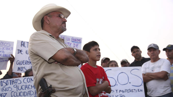 In this May 19, 2013 photo, Hipolito Mora, leader of a local self-defense movement, stands with a side-arm as residents protest extortion fees and kidnappings by the Knights of Templar drug cartel in La Ruana, Mexico.  Self-defense groups started to spring up in February to fight back the Knights Templar drug cartel which is extorting protection payments from cattlemen and lime growers, butchers and even marijuana growers.  The federal government sees both the self-defense forces and the cartel as dangerous enemies. (AP Photo/Marco Ugarte)