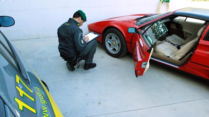 This undated handout photo provided on Oct. 24, 2012 by the the Guardia di Finanza, Italy's financial police corps, shows a tax police officer next to a confiscated Ferrari, at the Guardia di Finanza quarters, in Pescara, Italy. Good plumbers might be worth their weight in gold, but when one was spotted zipping around near the town of Pescara in a bright red Ferrari, Italian tax police were fast on his trail. Eradicating entrenched, endemic tax evasion is crucial to Premier Mario Monti's quest to keep Italy from succumbing to the European debt crisis, and it is critical to fellow euro-zone members in more dire straits, such as Greece and Spain. (AP Photo/Courtesy of the Guardia di Finanza, ho)