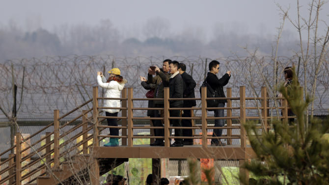 Visitors take their souvenir pictures near a military barbed-wire fence at the Imjingak Pavilion near the border village of Panmunjom, which has separated the two Koreas since the Korean War, in Paju, north of Seoul, South Korea, Wednesday, March 6, 2013. North Korea's military is vowing to cancel the 1953 cease-fire that ended the Korean War, straining already frayed ties between Washington and Pyongyang as the United Nations moves to impose punishing sanctions over the North's recent nuclear test. (AP Photo/Lee Jin-man)