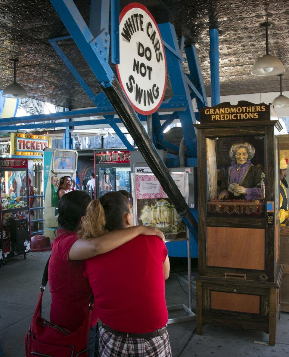 "This June 12, 2013 photo shows a couple looking at the 90-year-old fortune telling machine ""Grandma's Predictions,"" which was restored after damage in superstorm Sandy at the amusement park in the Coney Island neighborhood in the Brooklyn borough of New York. (AP Photo/Bebeto Matthews)"